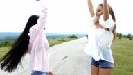 Cheerful young women dancing on the road,slow motion video