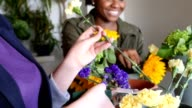Cheerful young women working in flower shop, creating bouquets of cut flowers video