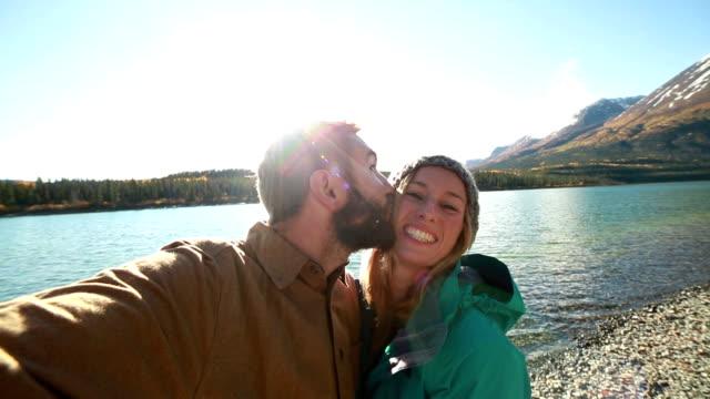 Cheerfull travellers taking selfies by lake video