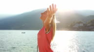 Cheering woman arms raised by the lake at sunset-Summer video