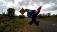 Cheering young man jumping mid-air on the road, Australia video