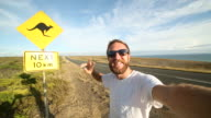 Cheering young man takes selfie portrait next to kangaroo sign video