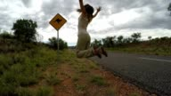 Cheering young woman jumping mid-air on the road, Australia video