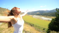 Cheering young woman on hill arms outstretched facing strong wind video