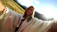 Cheering young woman takes a selfie portrait in nature video
