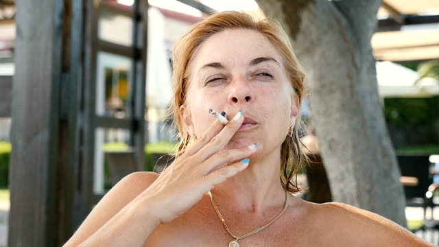 A cheery woman smiles and smokes a cigarette on a sea resort in a bar in slo-mo video