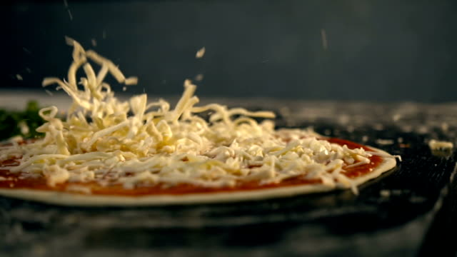 Cheese falls on pizza. Slow Motion video