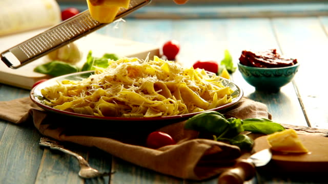Cheese grating Just cooked Pappardelle italian cuisine dish on the rustic table video