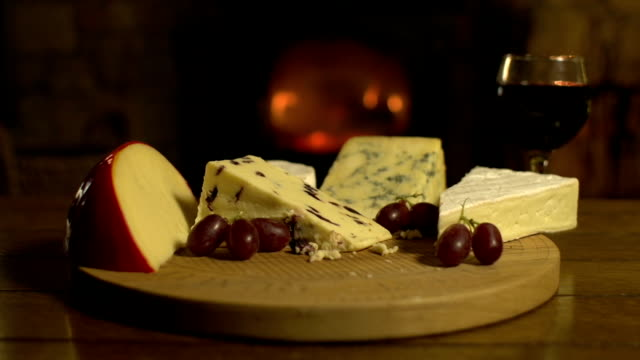Cheeseboard platter and wine on the Table, Fireplace behind video