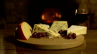 Cheeseboard with red wine in front of fire, DOLLY video
