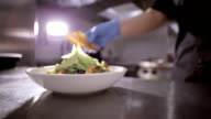 Chef adding toasts to fresh salad with lettuce, shrimps and cheeze. video
