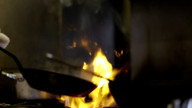 Chef cooks with a pan over a fire - CU, slow motion video