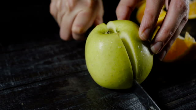 Chef Cuts Apple into Two Pieces on Dark Wood video