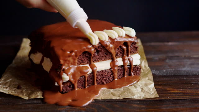 Chef decorate chocolate cake. Dessert decorating with pastry bag video