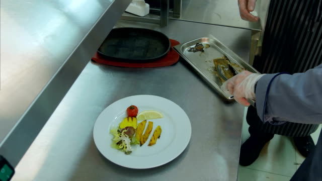 Chef explaining cook trainee how to put fish on a plate with vegetables video