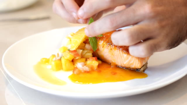 Chef Garnishing fried salmon in the orange sauce with peppermint video