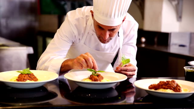 Chef garnishing pasta dish with basil leaf video