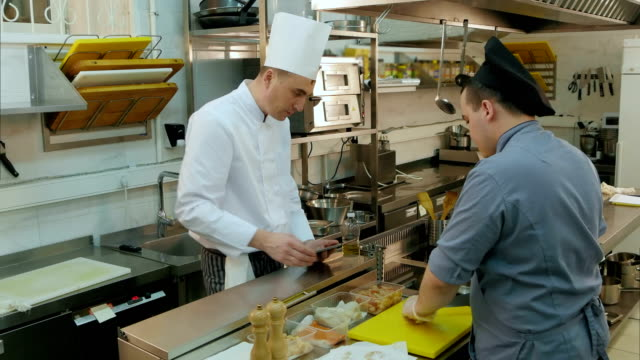 Chef holding tablet and instructing his trainee how to chop mushroom video