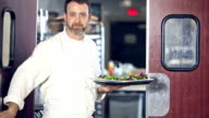 Chef in restaurant opens door to kitchen with food tray video
