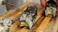 chef in restaurant preparing and Cutting sushi rolls healthy food video