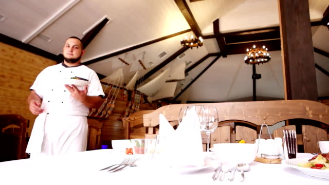 Chef invites you to the festive table in the restaurant, the chef in the Café hall bears a plate of food, a portrait of a chef in a culinary form, the table video