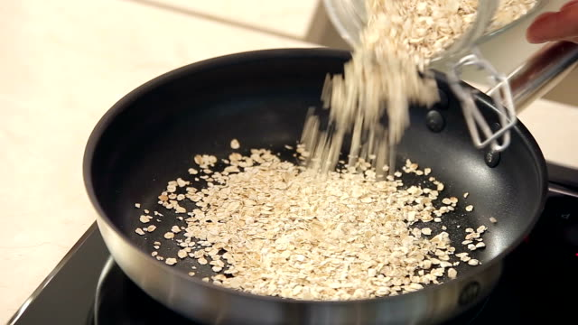 Chef is Drying Oat-Flakes on a Frying Pan video