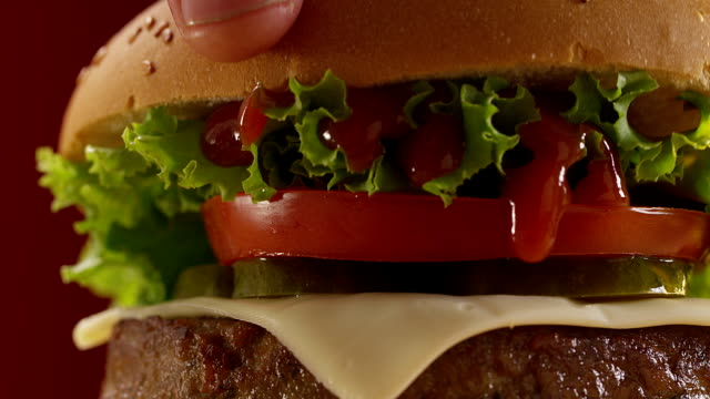 Chef makes burger on red background. Shot on RED EPIC Cinema Camera. video