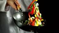 Chef making vegetable stir fry in wok video