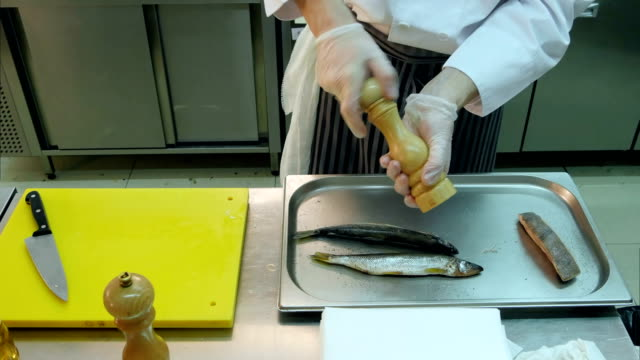 Chef peppering and salting fish on a tray video