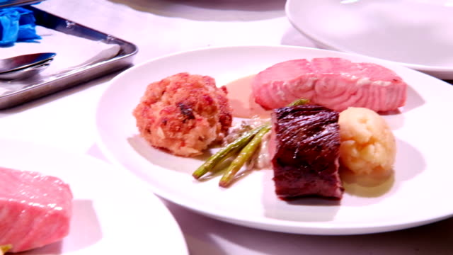 chef place fried crab ball, grilled salmon fillet, roasted beef steak, asparagus and mashed potatoes puree on plate ready to serve. Tasty and delicious homemade cuisine, restaurant menus, healthy eating concept video