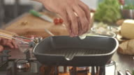 Chef placing raw steak into frying pan video