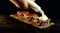 Chef pouring cream for cupcakes decorating. Baking muffins. Muffins decoration video