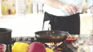 Chef pouring red wine into frying pan video