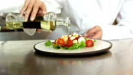 Chef pouring salad dressing over a salad video