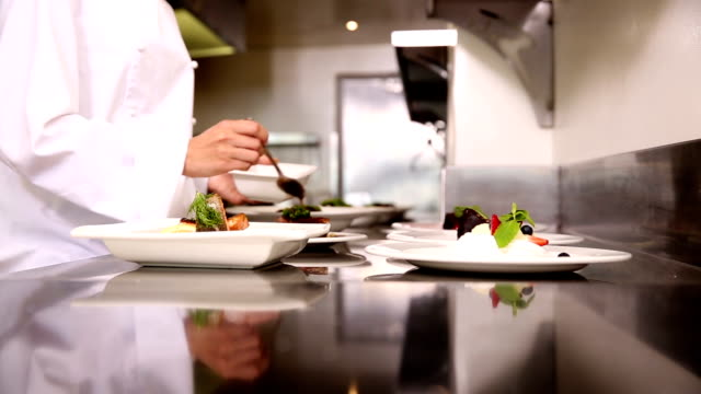 Chef pouring sauce over dishes video