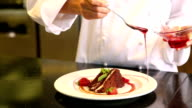 Chef pouring strawberry sauce over chocolate cake video