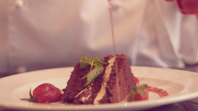 Chef pouring syrup over chocolate dessert video