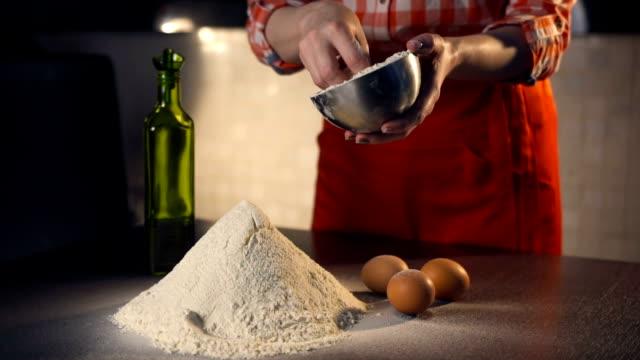 Chef pours flour for pizza. Slow motion video