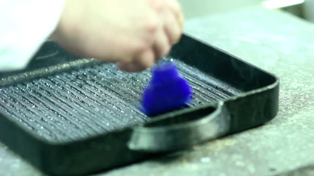 Chef pours olive oil on a grill pan video