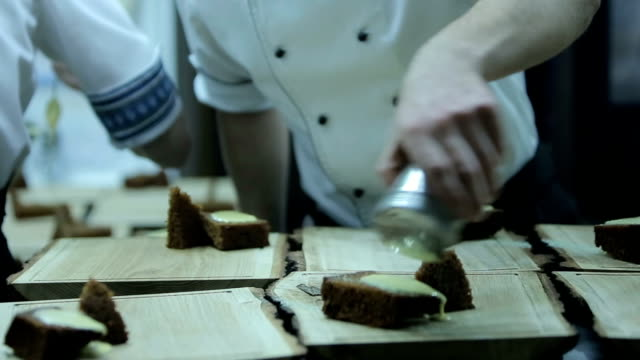 Chef prepares a dessert in a restaurant kitchen. Close up, dish presentation video