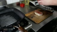 Chef preparing and spicing steak ready for cooking on grill video