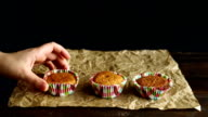 Chef put cupcakes on baking paper. Hand lay out vanilla cupcakes video