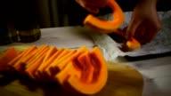 Chef put cut pumpkin on baking tray. Pumpkin dish preparing. Vegetable cooking video