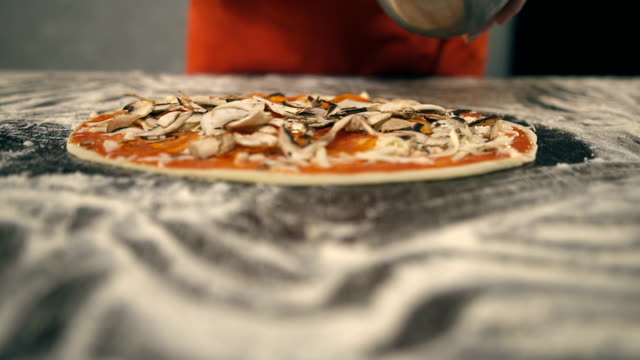 Chef puts champignons on the pizza. Slow Motion video