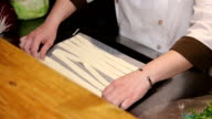 Chef puts sticks of dough on a baking tray video