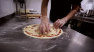 Chef putting cheese topping on his pizza base. video
