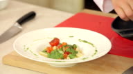 Chef Putting Fried Red Cherry Tomatoes on Pasta with Green Pesto in a Plate video