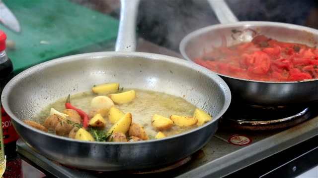 Chef roasting potato wedges with herbs in sunflower oil. video