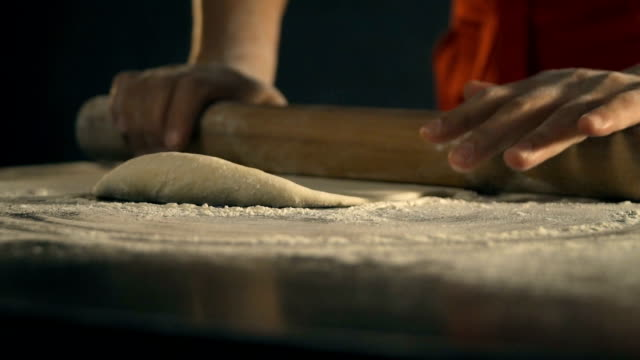 Chef rolling dough for pizza. Slow Motion video