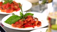 chef runs a fish dish in a tomato sauce with sunflower oil. video